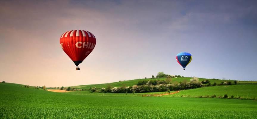两个蓝色和红色热气球在绿草和蓝天之下在白天高清壁纸