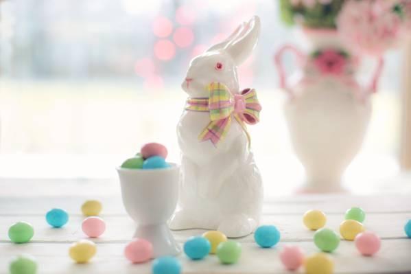 在蛋糖果旁边的白色陶瓷兔子小雕象HD墙纸