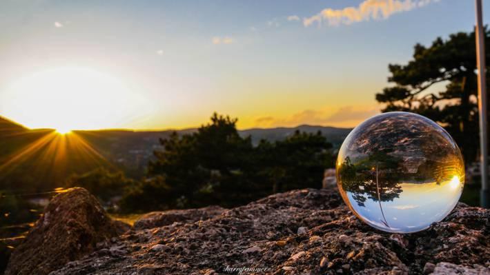 在日落时高清壁纸清除玻璃球附近的树木
