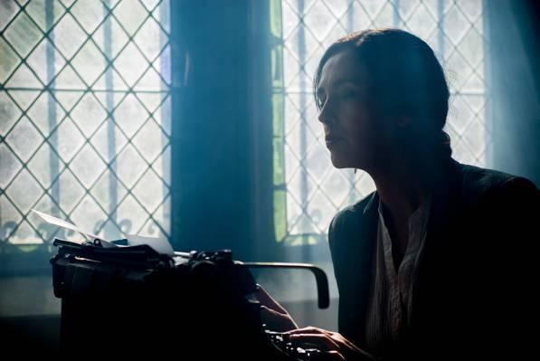 女子坐在黑暗的房间内的打字机附近高清壁纸