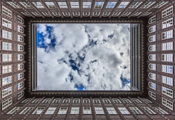 在白色云彩下的棕色高层建筑低角度摄影高清壁纸