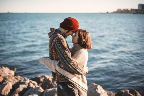 夫妇站在海边即将亲吻白色的天空下高清壁纸
