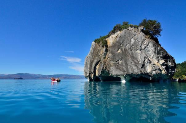 一群人在船附近大灰色岩石顶部的水的高清壁纸