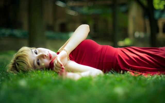 女人穿着红色躺在绿草高清壁纸的景深