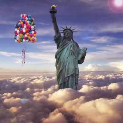 编辑照片的女人拿着束氦气球漂浮在自由女神像的高清壁纸的云层上面