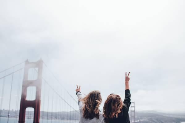 白天高清壁纸期间,两个女人在金门大桥附近投掷和平标志