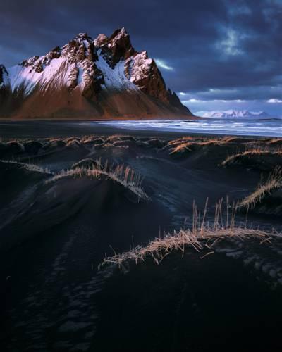 棕色和白色的山,被灰色的天空下的海洋附近的雪覆盖高清壁纸