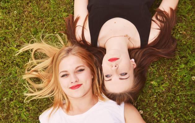 两个女人穿着黑色和白色无袖上衣躺在绿草的高清壁纸