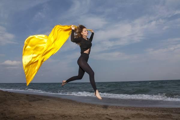女人穿着黑色的毛衣和紧身裤,拿着黄色的披肩,在白天高清壁纸海边跳跃