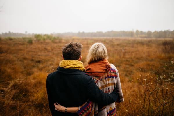 男子手持棕色草地场高清壁纸的女人的选择性焦点摄影