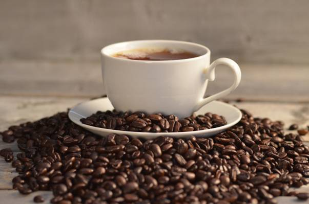 咖啡豆和茶碟之间桌上的咖啡豆高清壁纸
