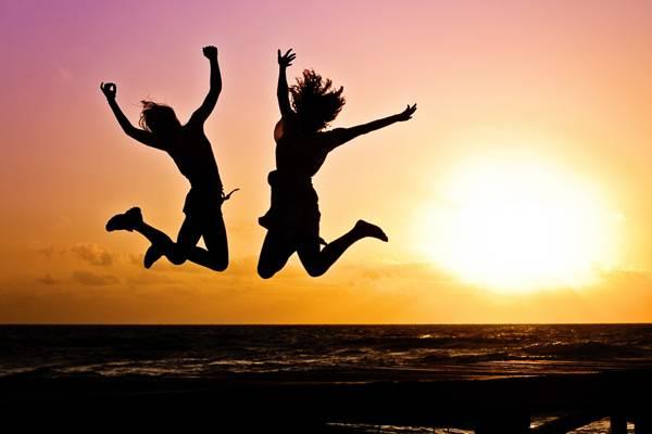 两个女人在海边反对日落高清壁纸跳跃