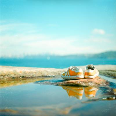 在岩石高清壁纸上的橙色和白色阿迪达斯低帮运动鞋