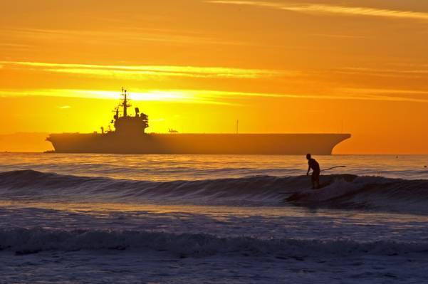 在日落时高清壁纸与船上的船体冲浪的人董事会剪影