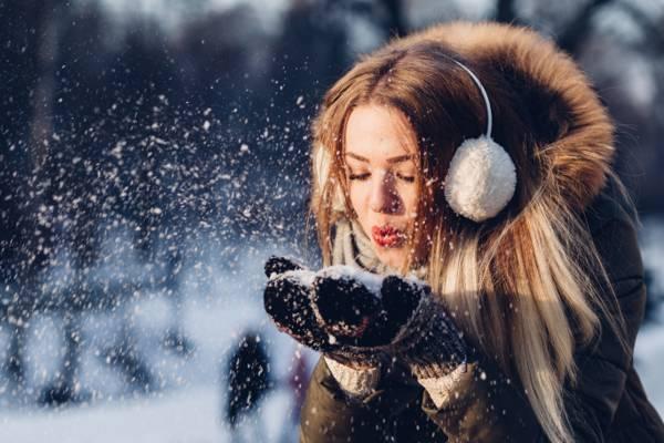女人穿着外套和耳套吹雪高清壁纸