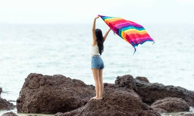 女人抱着披肩站在海边岩石附近的照片高清壁纸