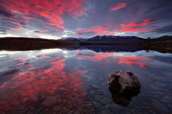 在红色日落高清壁纸期间水体上的褐色岩石