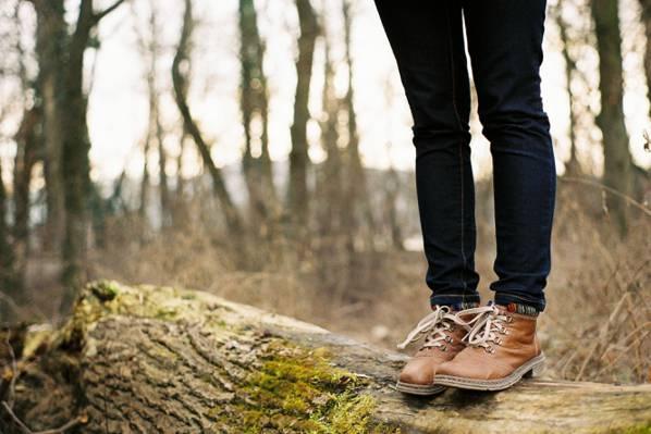 人穿着一双棕色皮靴站在棕色的火木头在白天时间高清壁纸