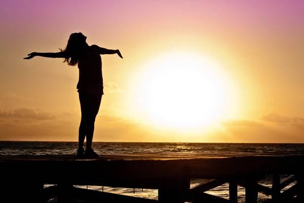 女人站在身旁的水高清壁纸的剪影