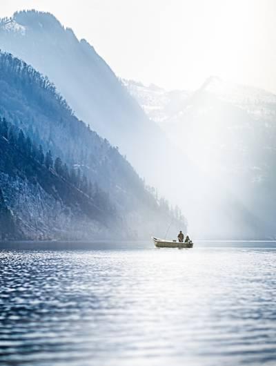 在白天高清壁纸山附近的海上的船上钓鱼的人