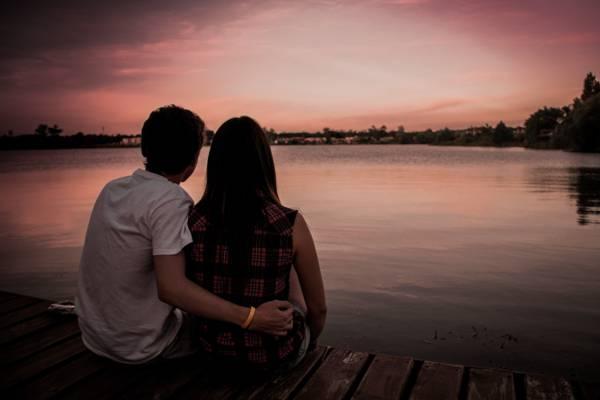 在黄昏时分坐在棕色的木制码头旁边的白衬衫的男人高清壁纸