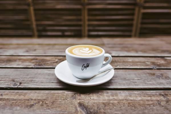 白色陶瓷茶杯旁边茶匙棕色木制的桌子上高清壁纸