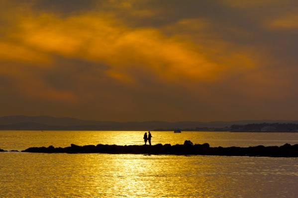 两个人在日落期间岛上的剪影高清壁纸