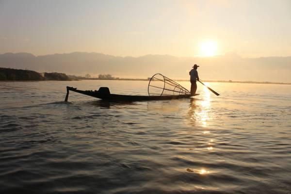 一艘渔夫在日落高清壁纸期间持有桨在水体的船上的剪影