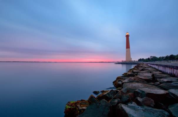 白色和红色的灯塔旁边镇静的身体的水高清壁纸