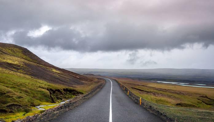 绿色的田野之间的灰色路面高清壁纸