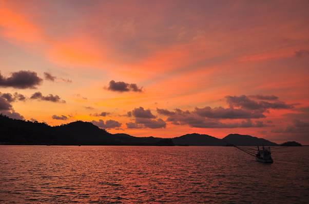 在多云的天空下帆船航行的山的轮廓颜色高清壁纸