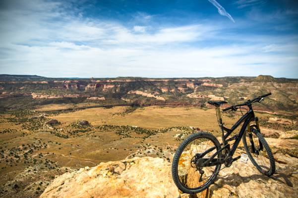 在棕色岩石表面上的黑色全悬挂自行车在白天高清壁纸
