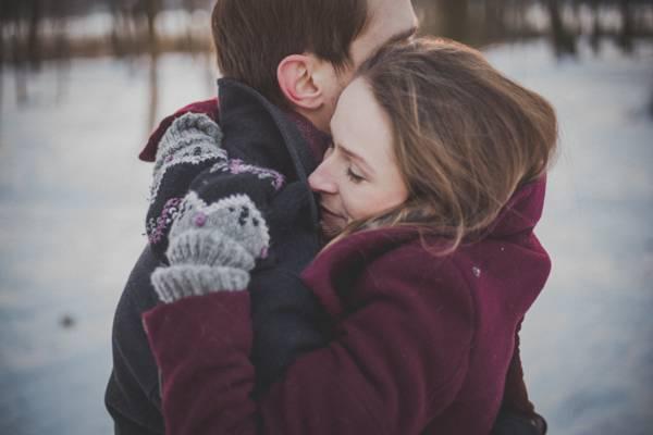 男人穿着黑色的雪外套拥抱女人穿着栗色雪外套高清壁纸