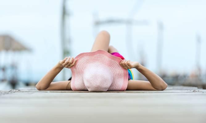 女子躺在路上抱着她的太阳帽高清壁纸的选择性焦点
