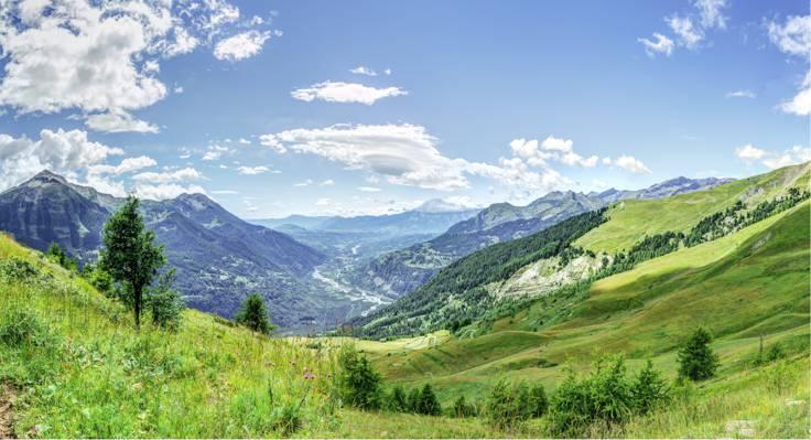 绿草领域和树的风景照片与在nimbus云下的山在白天高清墙纸之间